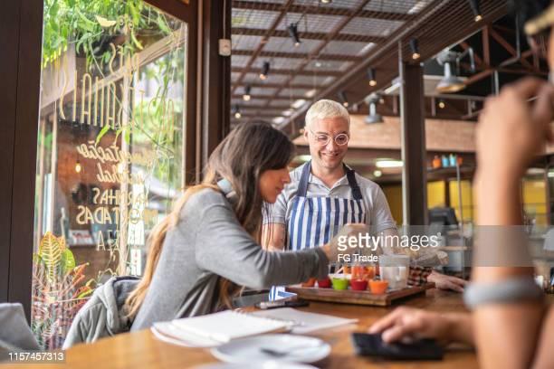 alimento do serviço do empregado de mesa aos clientes em um restaurante - foco no segundo plano - fotografias e filmes do acervo