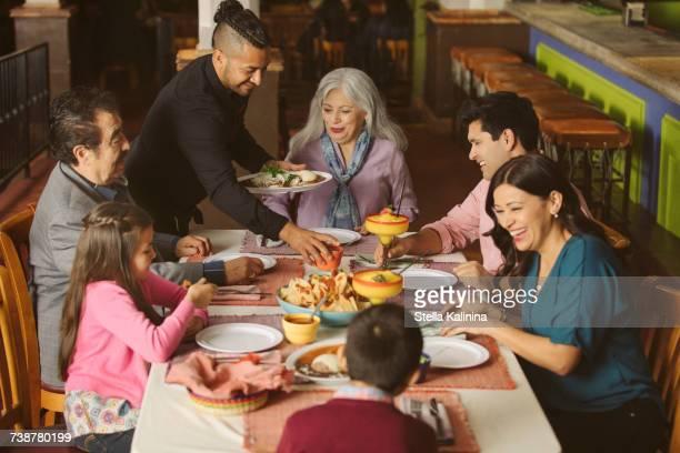 waiter serving food to family in restaurant - margarita seven photos et images de collection
