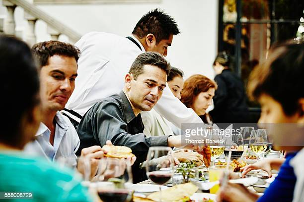 Waiter serving food to multi-generational family