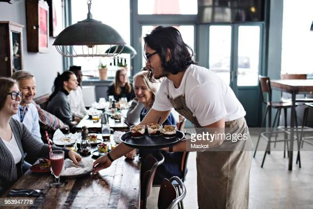 waiter serving food to smiling customers at restaurant - waiter stock pictures, royalty-free photos & images