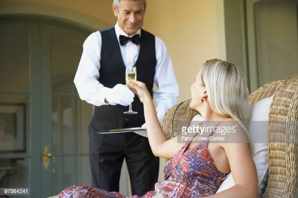 Waiter serving glass of champagne to woman