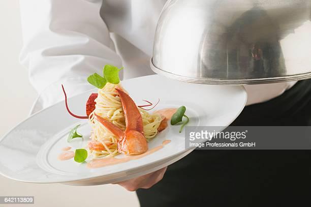 Waiter serving linguine with lobster