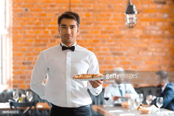 kellner serviert pizza - izusek stock-fotos und bilder