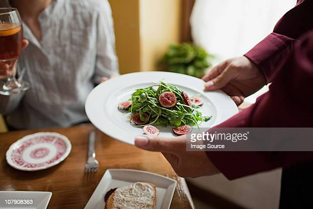 Waiter serving plate of salad