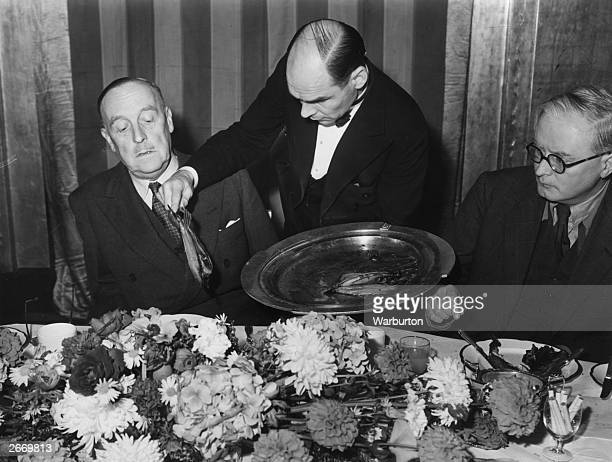 A waiter serving Sir Frederick Bell Chairman of the Herring Industry Board with kippers at a Kipper Breakfast at Claridge's Hotel London The aim of...