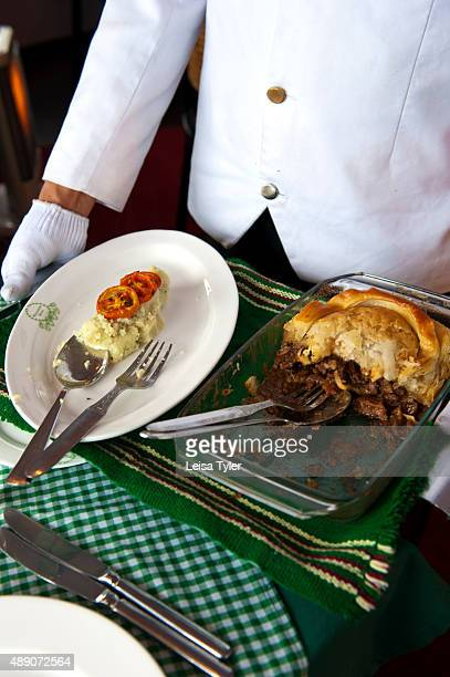 A waiter serving steak and kidney pie with mashed potatoes and grilled tomatoes at the colonial era Windamere Hotel in Darjeeling India
