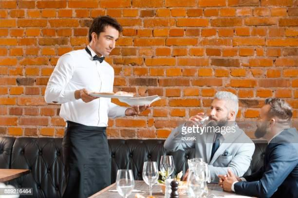kellner servieren für geschäftsleute im restaurant - izusek stock-fotos und bilder