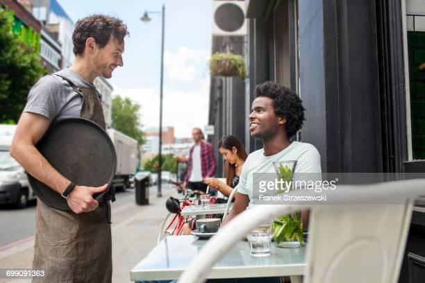 Waiter serving young man at city sidewalk cafe