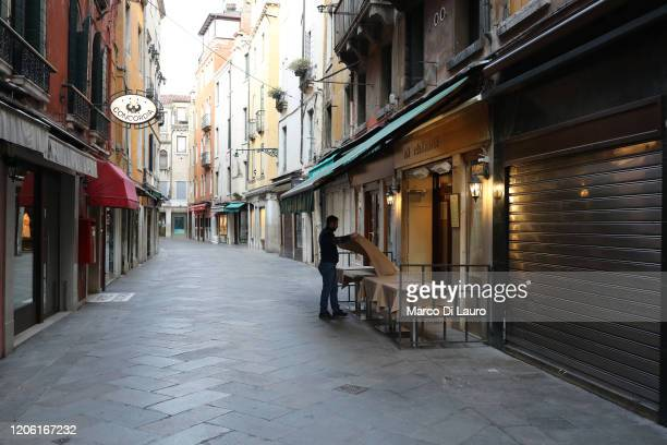 """Waiter sets a table in a restaurant on an empty street on March 9, 2020 in Venice, Italy. Prime Minister Giuseppe Conte announced a """"national..."""