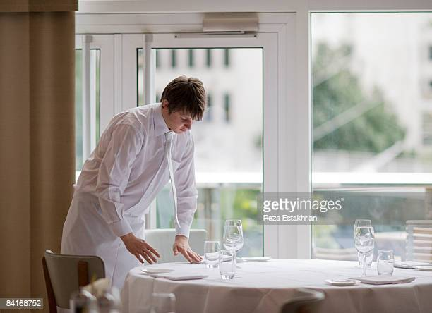 Waiter sets flatware in precise positions