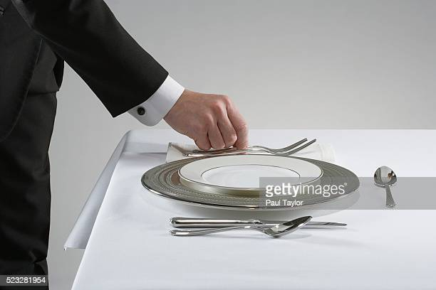 Waiter setting the table with fine china and silver