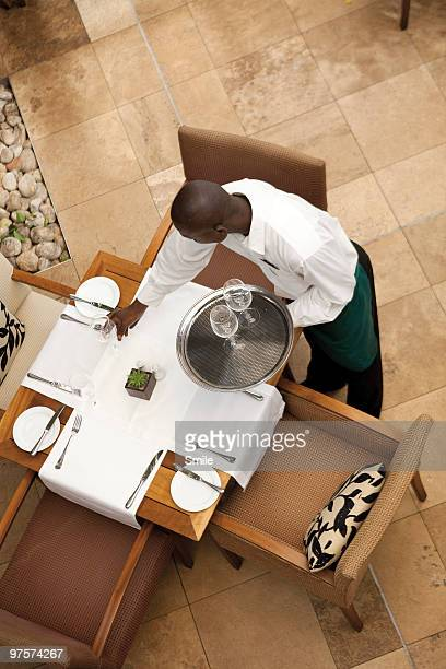 Waiter setting up table