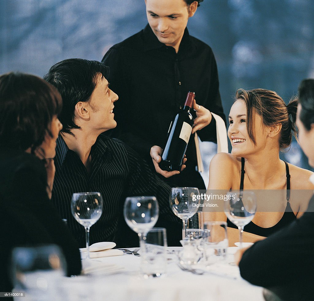 Waiter Showing a Bottle of Red Wine to a Group of Young, Smiling Adults Sitting at a Table at a Restaurant : Stock Photo