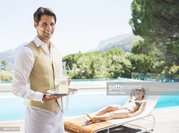 Waiter smiling at poolside