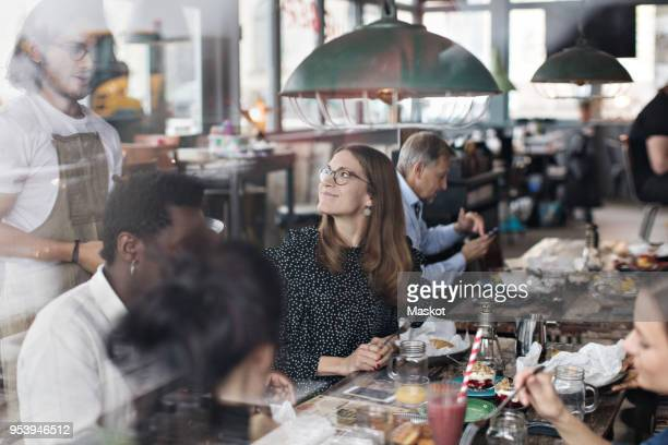 Waiter standing by customers at restaurant seen from window