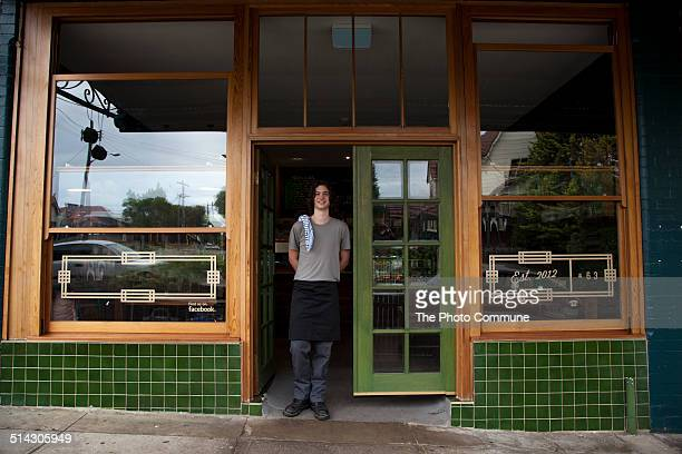 Waiter standing in front of restaurant or cafe