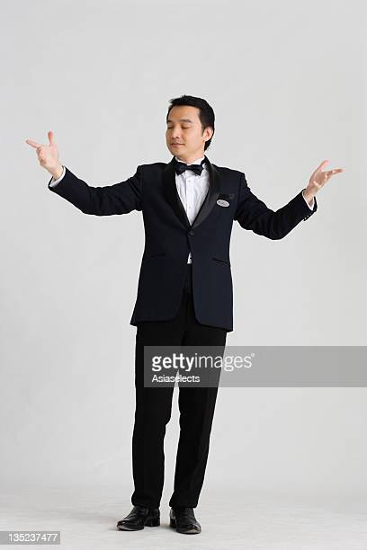 Waiter standing with his eyes closed and greeting