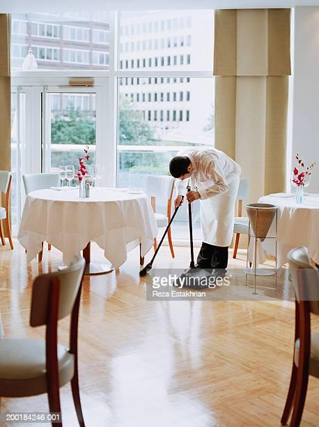 Waiter sweeping restaurant