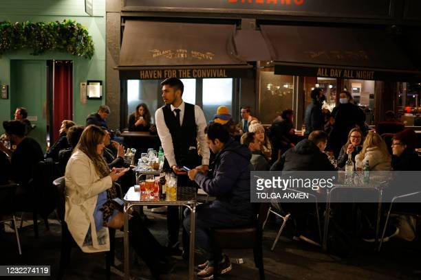 Waiter takes payment from customers at a table outside a bar in the Soho area of London, on April 12, 2021 as coronavirus restrictions are eased...