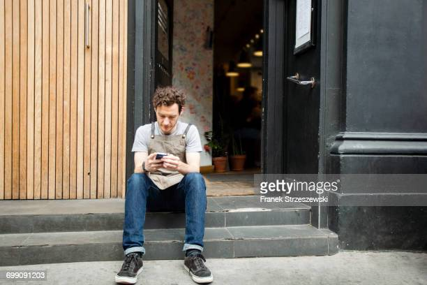 Waiter taking a break on cafe step looking at smartphone