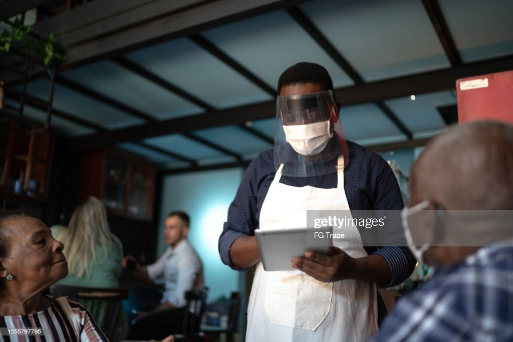 Waiter taking client's order, using a digital tablet in a restaurant : Stock Photo