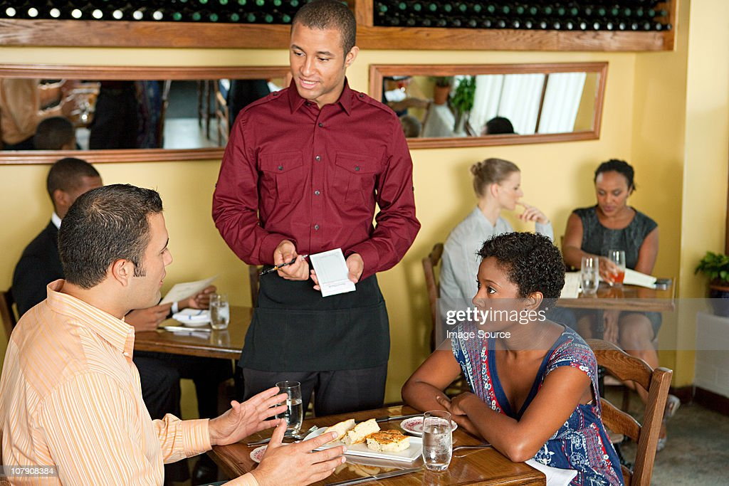Waiter taking customer orders in restaurant : Stock Photo