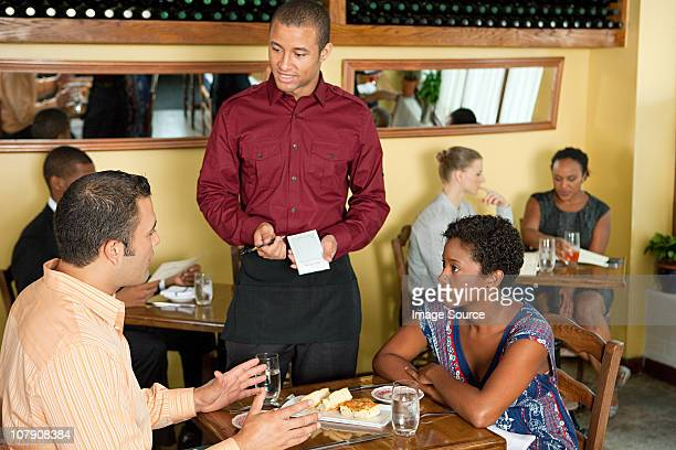 Waiter taking customer orders in restaurant