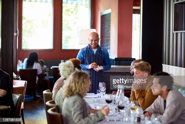 waiter taking customers' orders in restaurant - medium group of people stock pictures, royalty-free photos & images