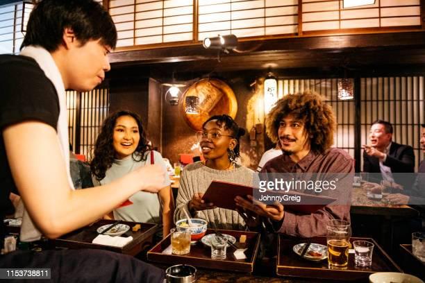 日本料理店で友達から料理を注文するウェイター - 観光客 ストックフォトと画像
