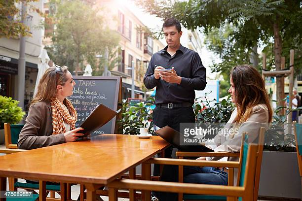 waiter taking order from female customers - klaus vedfelt mallorca stock pictures, royalty-free photos & images