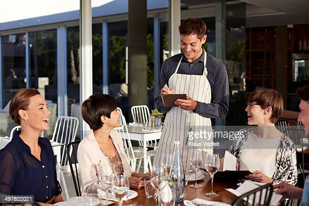 Waiter taking order from group of friends
