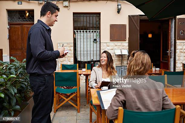 waiter taking order from two women - bucht stock-fotos und bilder