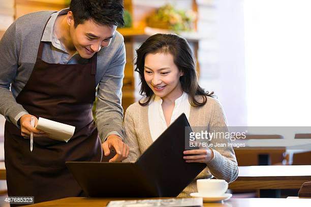 Waiter taking order from woman at restaurant