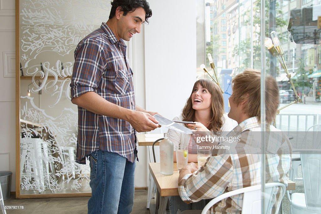 Waiter taking order in restaurant : Stock Photo