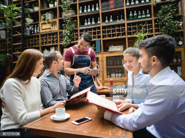 waiter taking order to a group at a restaurant using a tablet - menu stock pictures, royalty-free photos & images