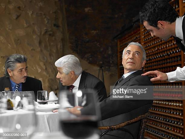 Camarero hablando de hombre de negocios con colegas en el restaurante