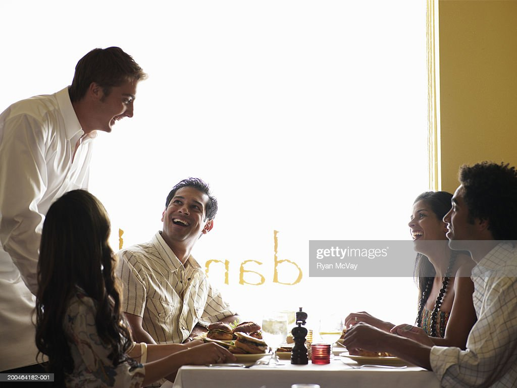 Waiter talking to four adults in restaurant, side view : Stock Photo