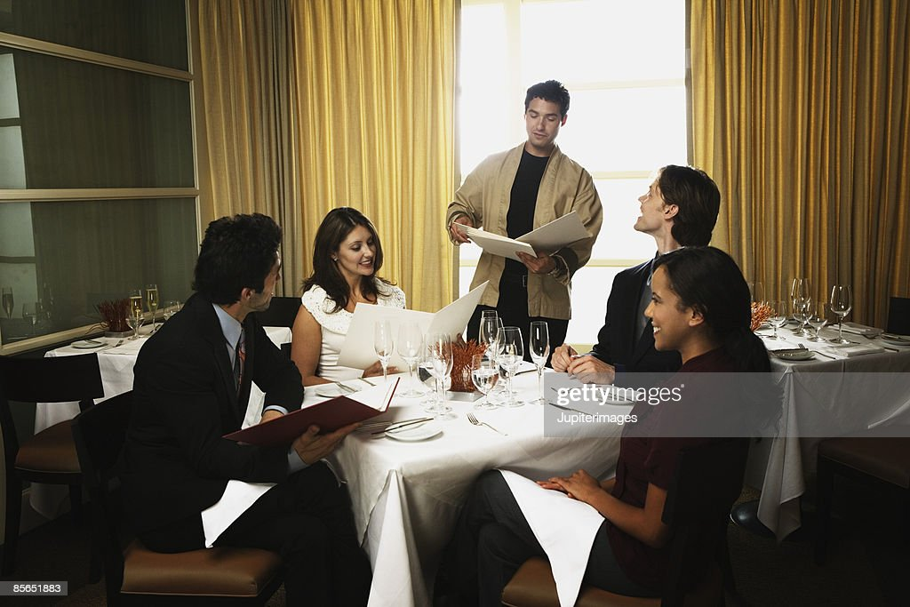 Waiter Talking With Restaurant Customers Stock Photo - Getty