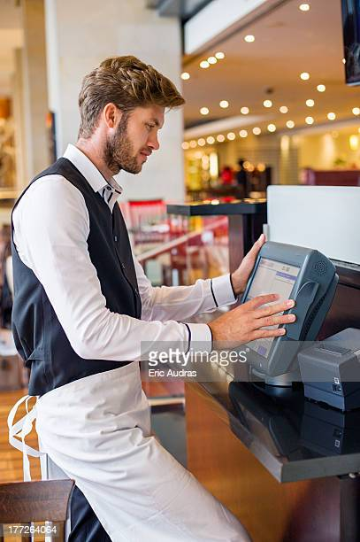 Waiter using a computer at checkout counter in a restaurant