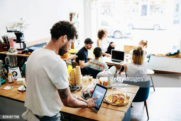Waiter Using Social Media To Promote His Busy City Cafe