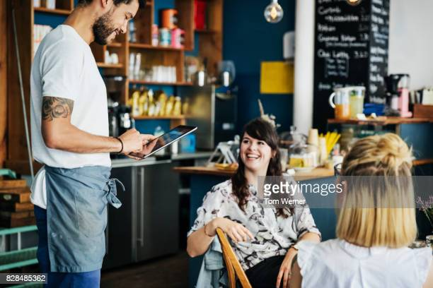 waiter using tablet to take orders from customers in coffee shop - waiter stock pictures, royalty-free photos & images