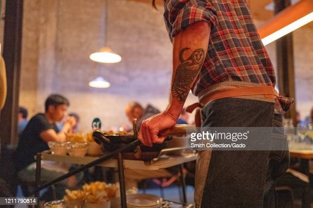 A waiter viewed from behind pushes a dim sum style cart of farm to table California cuisine menu items at State Bird Provisions a Michelin starred...