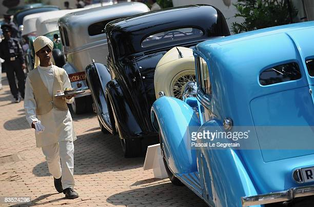 A waiter walks by a row of ventage cars on display during the 'Travel With Style' Concours at Royal Western India Turf Club on November 1 2008 in...