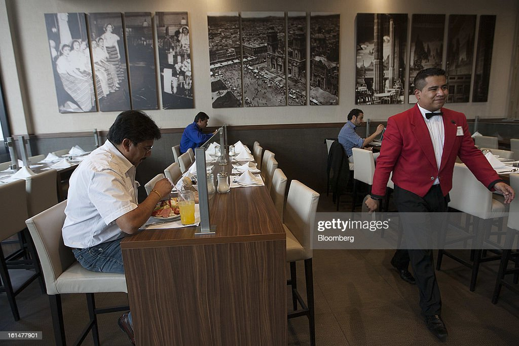 A waiter walks past customers eating lunch at a Grupo Sanborns SAB cafe in the Plaza Carso development in Mexico City, Mexico, on Friday, Feb. 8, 2013. Grupo Sanborns SAB, the retailer controlled by Mexican billionaire Carlos Slim, raised 10.5 billion pesos ($825 million) in an initial public offering (IPO) last week and the total could climb to 12.1 billion pesos including an overallotment option for underwriters. Photographer: Susana Gonzalez/Bloomberg via Getty Images