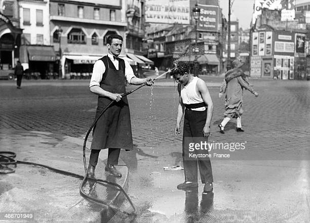 Waiter watering young boy during the heatwave in 1928 in Paris France