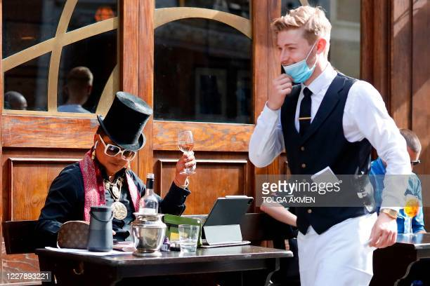 Waiter wearing a face mask or covering due to the COVID-19 pandemic, passes a customer drinking outside a restaurant in London on August 3 as the...