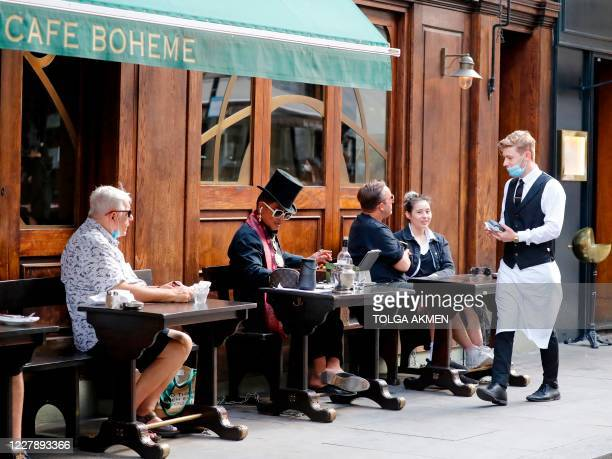Waiter wearing a face mask or covering due to the COVID-19 pandemic, takes orders from customers sat outside a restaurant in London on August 3 as...
