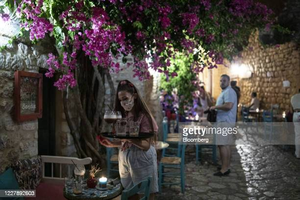 Waiter wearing a face mask prepares a table in a bar in the town of Areopoli on the Mani Peninsula, Laconia, Peloponnese region, Greece on Wednesday...