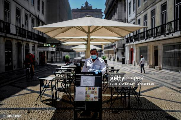 A waiter wearing a face mask waits for clients at a restaurant terrace after the relief of emergency measures due to the COVID19 outbreak in Lisbon...
