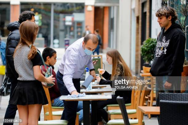 A waiter wearing a face mask wipes down a table before seating customers at a restaurant in central London on July 6 2020